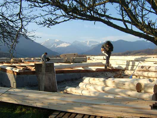 The D188 log cabin kit - beingg constructed with a beautiful view of the Alps, behind.